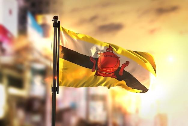 Bandiera brunei contro la città sfocata di sfondo all'alba retroilluminazione