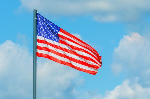 Bandiera degli stati uniti d'america con cielo blu nuvoloso.