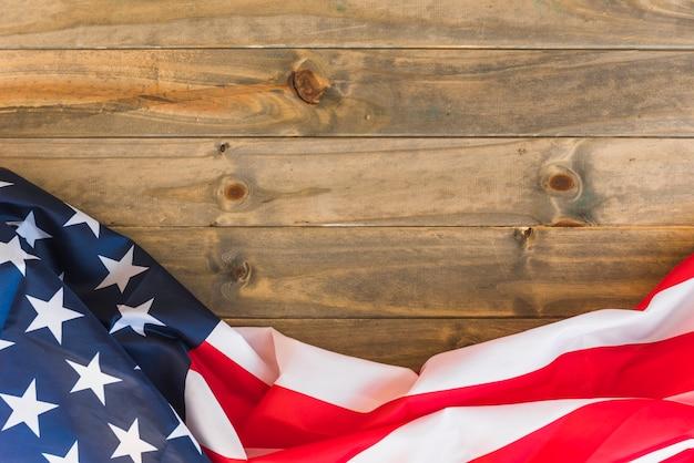Bandiera degli stati uniti del tessuto su superficie di legno