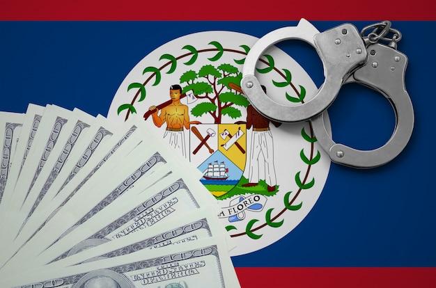 Bandiera del belize con manette e un pacco di dollari. il concetto di operazioni bancarie illegali in valuta statunitense