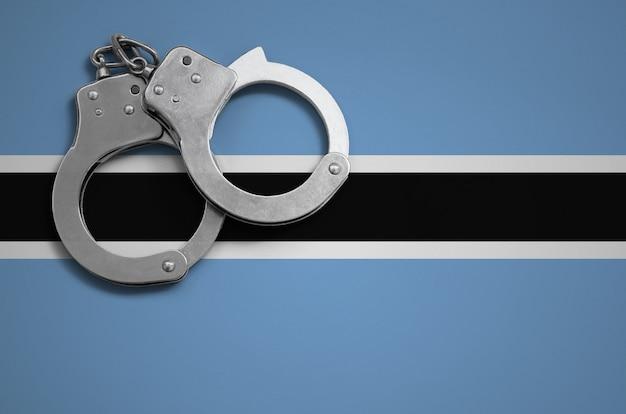 Bandiera del botswana e manette della polizia. il concetto di criminalità e reati nel paese