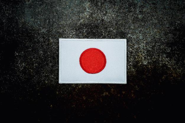 Bandiera del giappone sul pavimento di metallo abbandonato arrugginito nel buio.