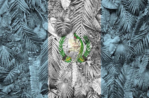 Bandiera del guatemala raffigurata su molte foglie di palme monstera. tessuto alla moda