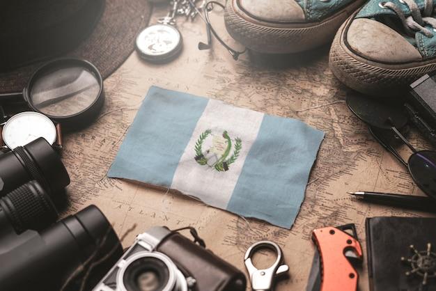 Bandiera del guatemala tra gli accessori del viaggiatore sulla vecchia mappa vintage. concetto di destinazione turistica.