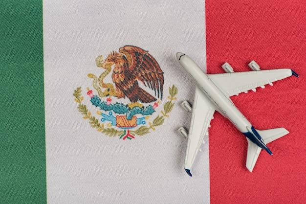 Bandiera del messico e aeroplano di modello. ripresa dei voli dopo la quarantena. viaggia in messico
