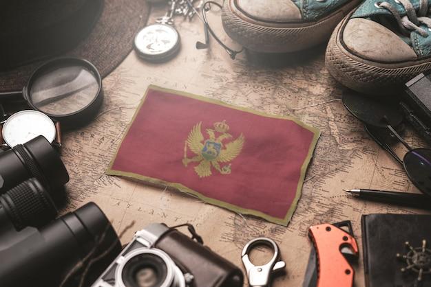 Bandiera del montenegro tra gli accessori del viaggiatore sulla vecchia mappa d'annata. concetto di destinazione turistica.