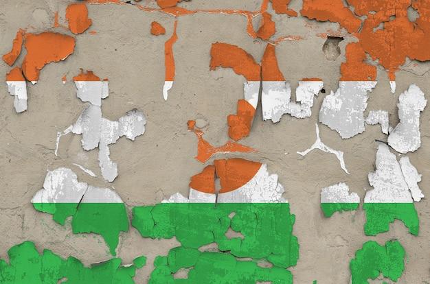 Bandiera del niger raffigurata nei colori della vernice sul vecchio primo piano sudicio disordinato obsoleto del muro di cemento. banner con texture su sfondo ruvido