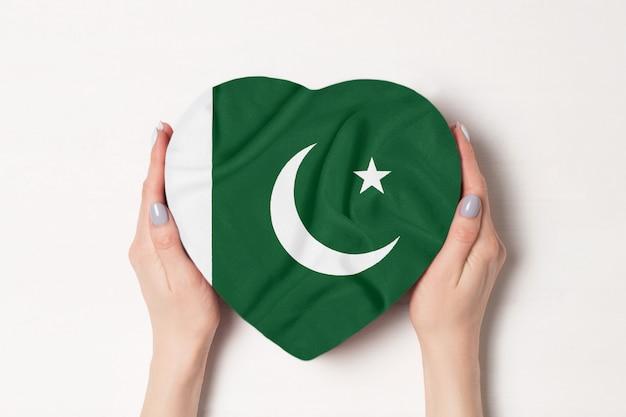 Bandiera del pakistan su una scatola a forma di cuore in mani femminili. bianca