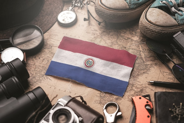 Bandiera del paraguay tra gli accessori del viaggiatore sulla vecchia mappa vintage. concetto di destinazione turistica.