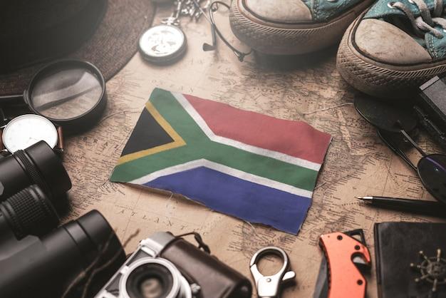 Bandiera del sudafrica tra gli accessori del viaggiatore sulla vecchia mappa d'annata. concetto di destinazione turistica.