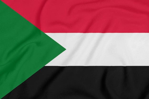 Bandiera del sudan su tessuto strutturato. simbolo patriottico