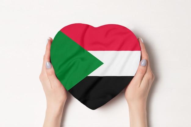 Bandiera del sudan su una scatola a forma di cuore in mani femminili.