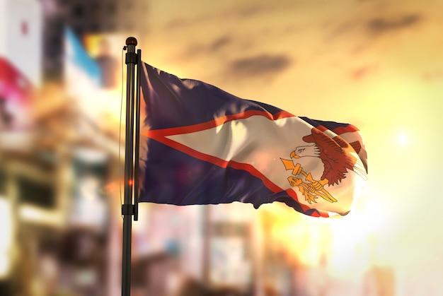 Bandiera dell'america americana contro la città sfocata di sfondo all'illuminazione di sunrise