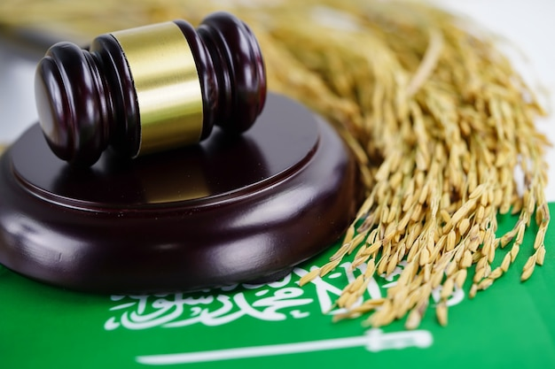 Bandiera dell'arabia saudita e martello del giudice con riso a grani d'oro.