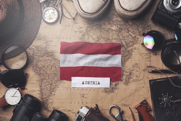 Bandiera dell'austria tra gli accessori del viaggiatore sulla vecchia mappa d'annata. colpo ambientale