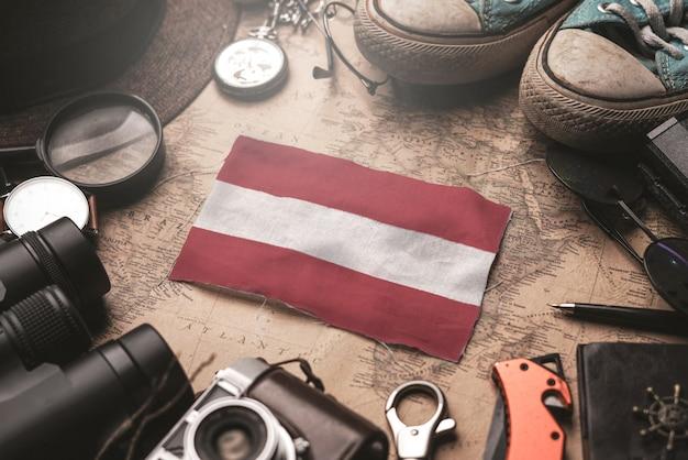 Bandiera dell'austria tra gli accessori del viaggiatore sulla vecchia mappa d'annata. concetto di destinazione turistica.