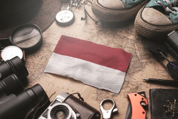 Bandiera dell'indonesia tra gli accessori del viaggiatore sulla vecchia mappa d'annata. concetto di destinazione turistica.