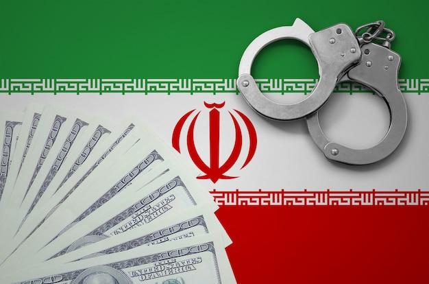 Bandiera dell'iran con le manette e un pacco di dollari. il concetto di operazioni bancarie illegali in valuta statunitense