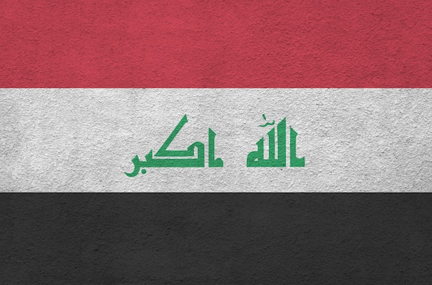 Bandiera dell'iraq raffigurata con colori vivaci della vernice sulla vecchia parete intonacata a rilievo.
