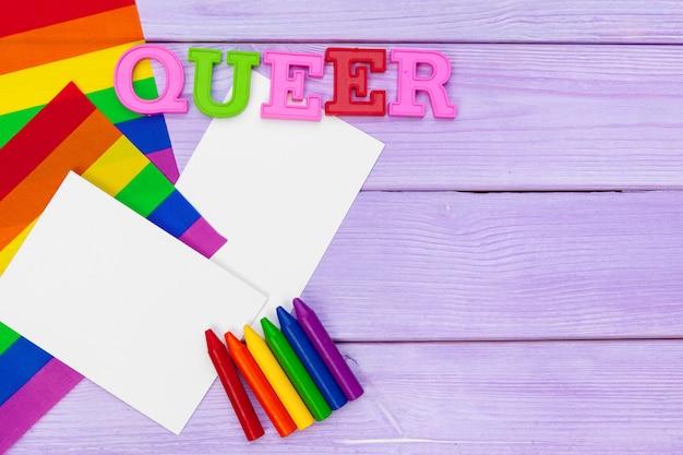 Bandiera dell'orgoglio gay sulla tavola e sul testo di legno - queer