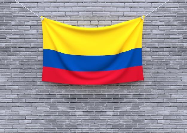 Bandiera della colombia che appende sul muro di mattoni