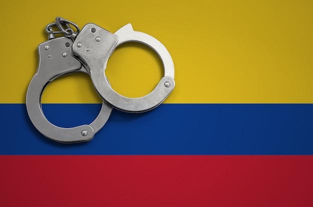 Bandiera della colombia e manette della polizia. il concetto di criminalità e reati nel paese