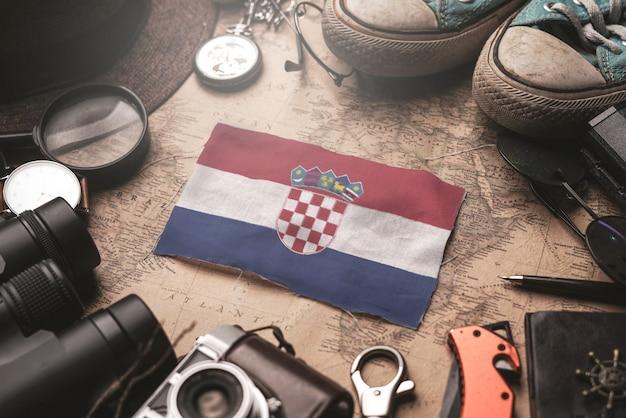 Bandiera della croazia tra gli accessori del viaggiatore sulla vecchia mappa vintage. concetto di destinazione turistica.