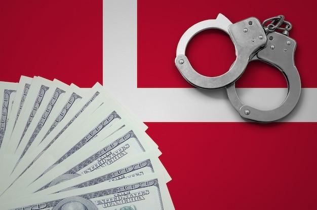 Bandiera della danimarca con le manette e un pacco di dollari. il concetto di operazioni bancarie illegali in valuta statunitense
