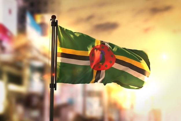 Bandiera della dominica contro la città sfocata di sfondo all'illuminazione di sunrise