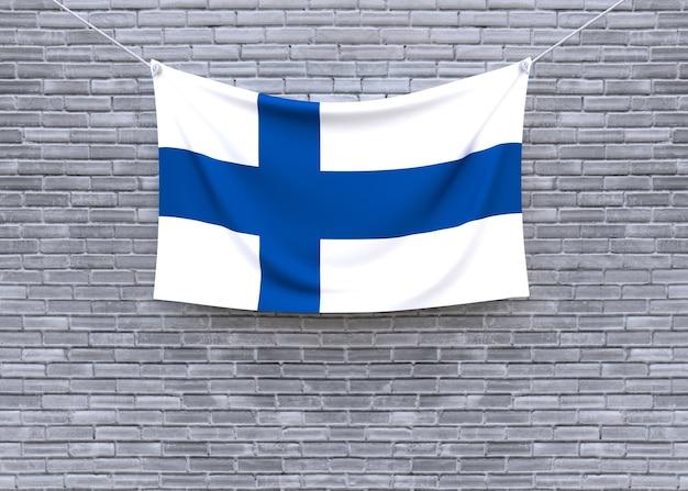 Bandiera della finlandia che appende sul muro di mattoni