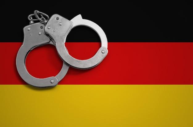 Bandiera della germania e manette della polizia. il concetto di criminalità e reati nel paese