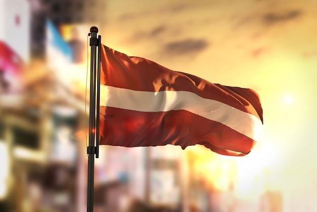 Bandiera della lettonia contro la città sfocata di sfondo al retroilluminazione di alba