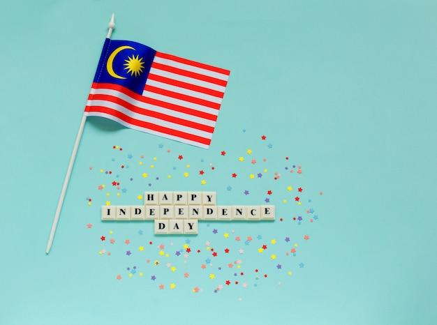 Bandiera della malesia con iscrizione della felice festa dell'indipendenza
