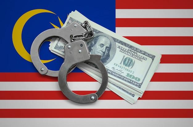 Bandiera della malesia con le manette e un pacco di dollari. corruzione valutaria nel paese. reati finanziari