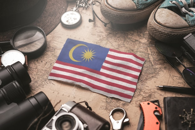 Bandiera della malesia tra gli accessori del viaggiatore sulla vecchia mappa d'annata. concetto di destinazione turistica.