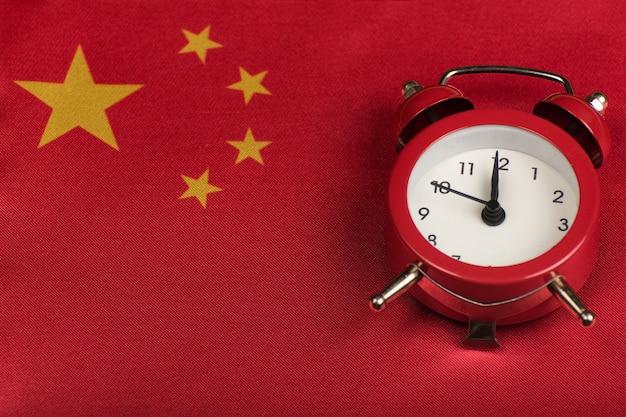 Bandiera della repubblica popolare cinese e sveglia vintage da vicino.