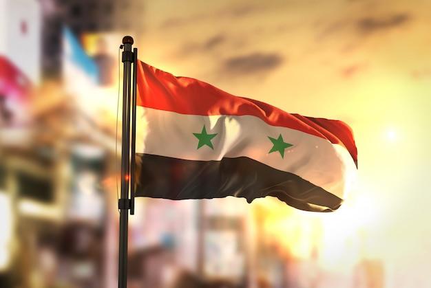 Bandiera della siria contro la città sfocata di sfondo all'illuminazione di sunrise