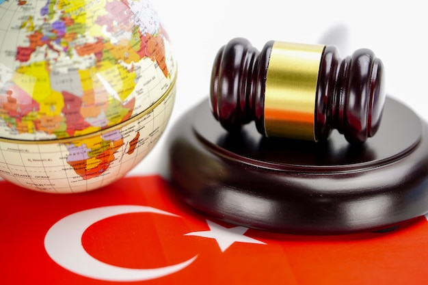 Bandiera della turchia e giudice martello con mappa del mondo globo. legge e giustizia concetto di tribunale.