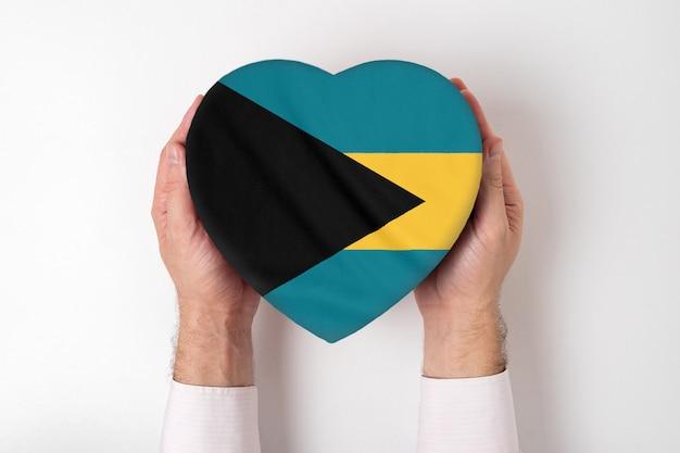 Bandiera delle bahamas su una scatola a forma di cuore in mani maschili.