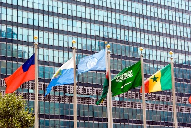 Bandiera delle nazioni unite e di altri paesi che salutano di fronte all'edificio della sede ufficiale.