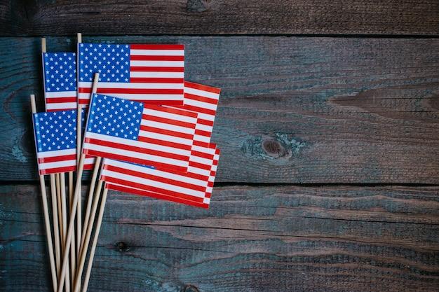 Bandiera di carta in miniatura usa. bandiera americana su fondo di legno rustico.