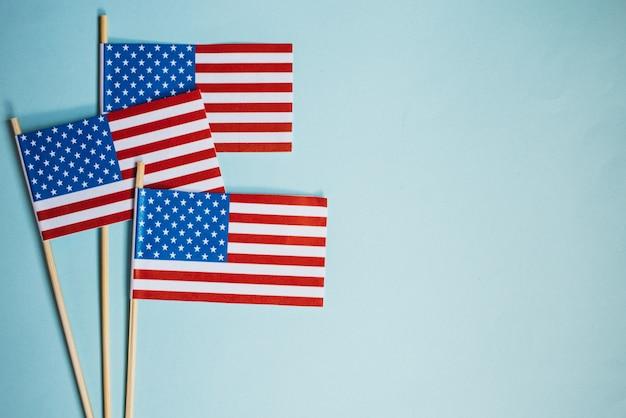 Bandiera di carta in miniatura usa. bandiera americana su sfondo blu.
