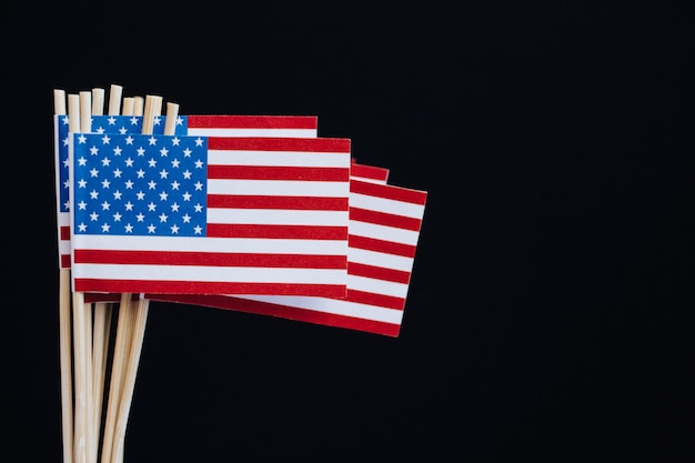 Bandiera di carta in miniatura usa. bandiera americana su sfondo nero.