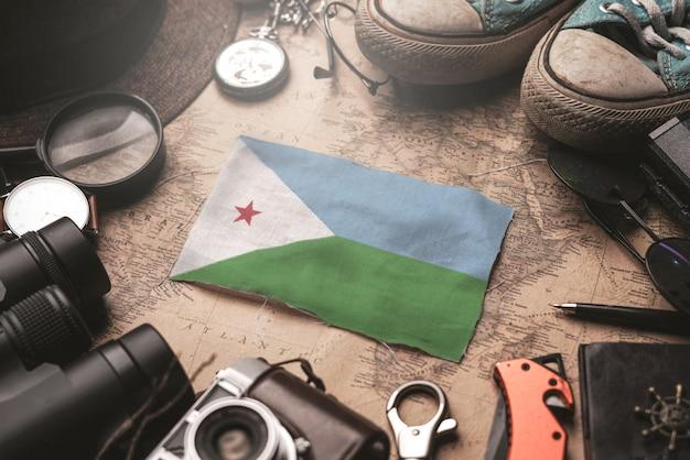 Bandiera di gibuti tra gli accessori del viaggiatore sulla vecchia mappa vintage. concetto di destinazione turistica.