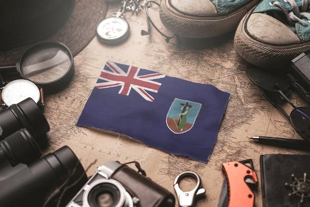 Bandiera di montserrat tra gli accessori del viaggiatore sulla vecchia mappa vintage. concetto di destinazione turistica.