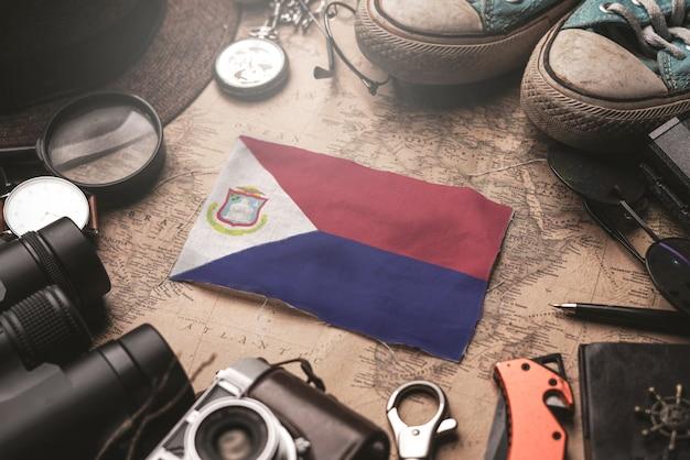 Bandiera di san martino tra gli accessori del viaggiatore sulla vecchia mappa vintage. concetto di destinazione turistica.