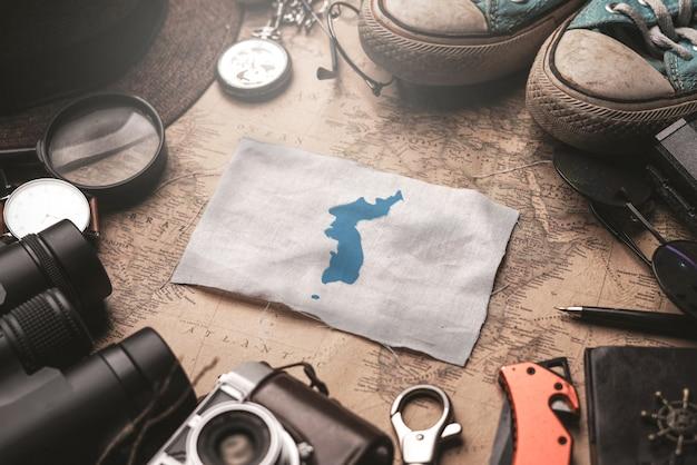 Bandiera di unificazione della bandiera della corea tra gli accessori del viaggiatore sulla vecchia mappa d'annata. concetto di destinazione turistica.