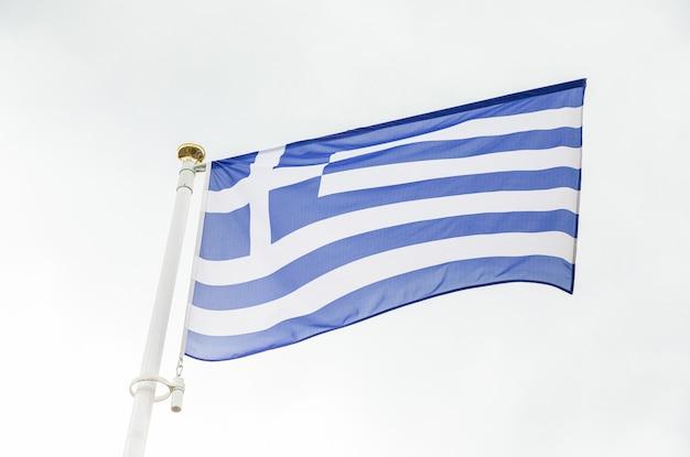 Bandiera greca che fluttua nel vento contro il cielo