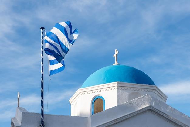 Bandiera greca e chiesa ortodossa a mykonos, in grecia