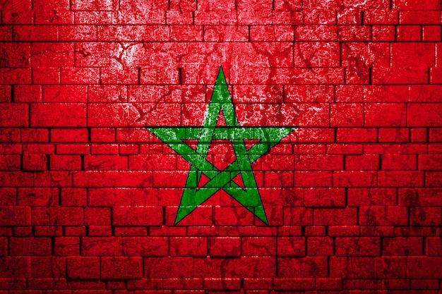 Bandiera nazionale del marocco su sfondo di muro di mattoni.